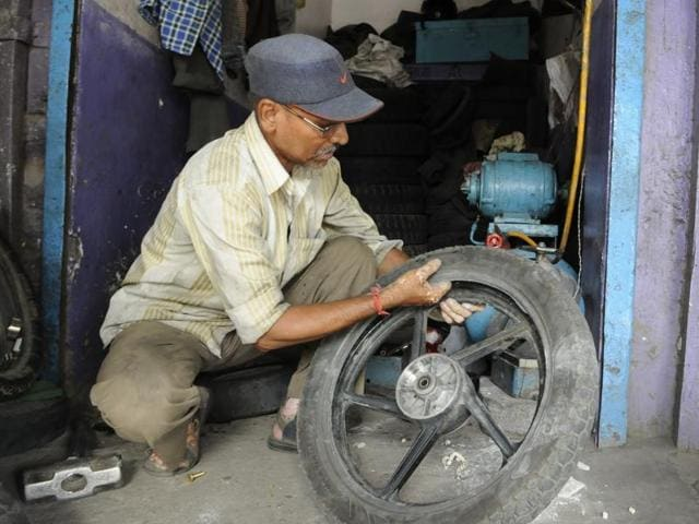 PN Deshmukh, father of AAP MLA Praveen Deshmukh, at his tyre repairing shop.