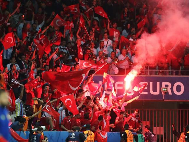 Turkey supporters wave the national flags and a flare during the Euro 2016 group D football match.