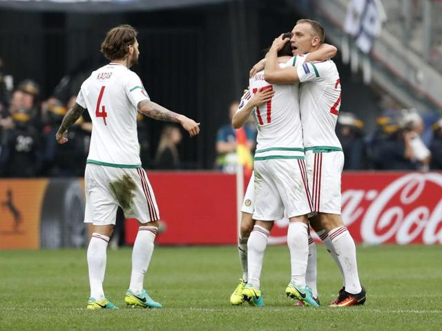 Birkir Saevarsson, on the ground, reacts after scoring an own goal and Hungary's first as Daniel Bode celebrates.