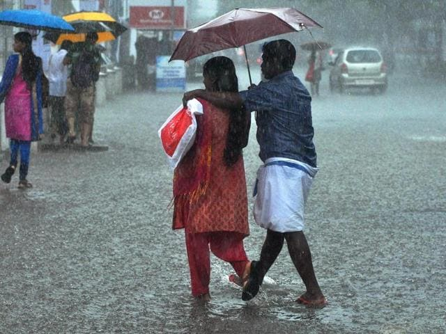 Two people cross a road during first monsoon showers in Kochi on Wednesday.