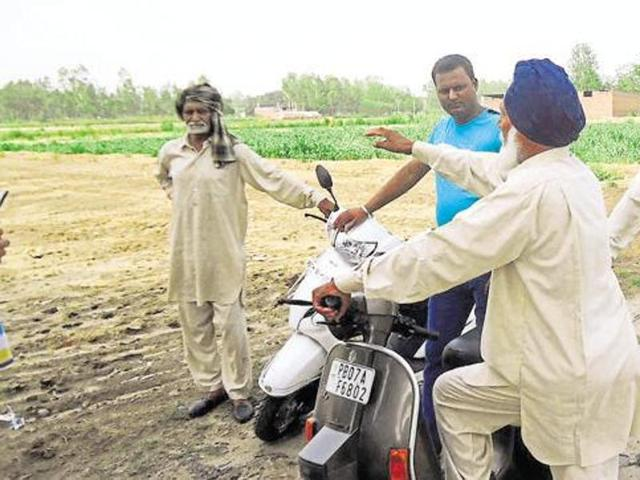 Farmers showing their agricultural land, which was purchased at throwaway rates, along the main road at Piplanwala village in Hoshiarpur.
