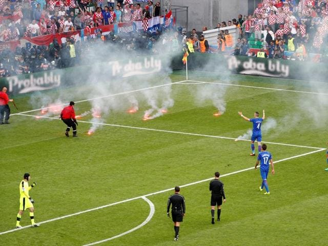 Stewards tend to flares that have been thrown onto the pitch by fans as players look on at Stade Geoffroy-Guichard, Saint-Étienne, France.
