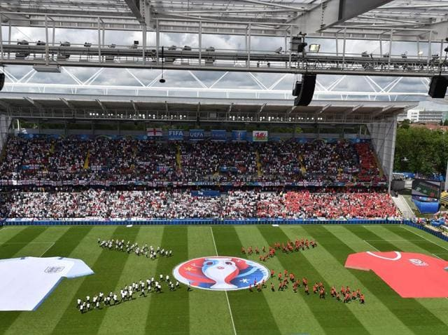 Volunteers perform with a flag showing the logo of the Uefa Euro 2016 football tournament prior to the Euro 2016 group B football match between England and Wales at the Bollaert-Delelis stadium in Lens.