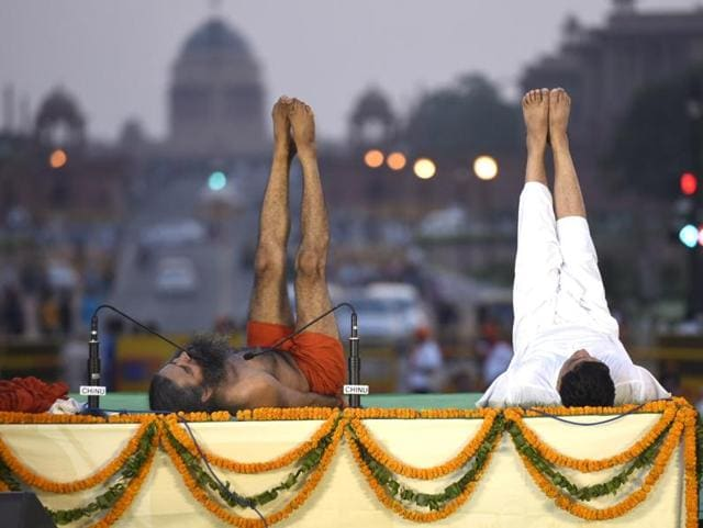 Ramdev and union minister Venkaiah Naidu practice Yoga along with others during a yoga camp ahead of the International Yoga Day on June 21, at Rajpath.