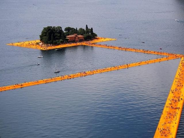 People walk on the monumental installation entitled 'The Floating Piers' created by artist Christo Vladimirov Javacheff on Iseo Lake, in northern Italy, on June 18, 2016.