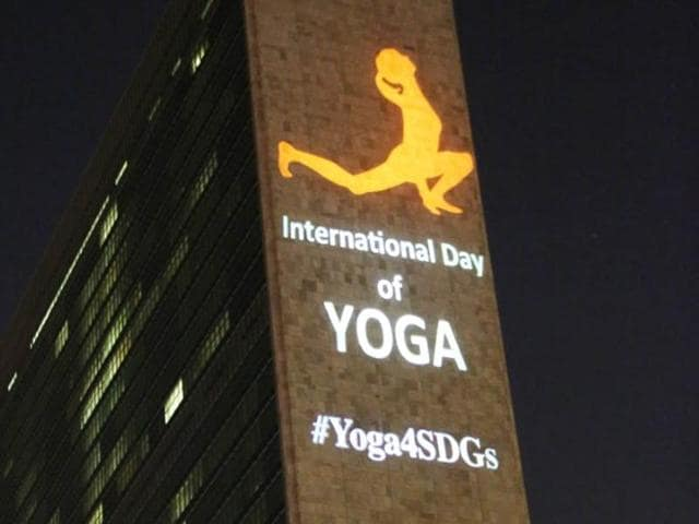 The image of a yoga posture is projected onto the United Nations headquarters in New York.