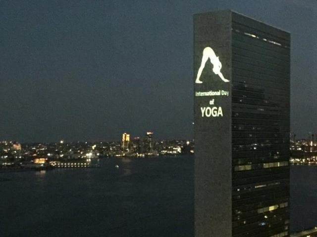 The image projected onto the UN building shows a woman doing the 'Parvatasana' or the 'inverted V' posture.