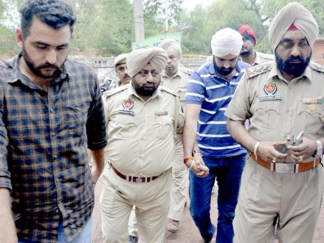Akali leader Rajbir Singh Bhullar (in white turban) and his aide Lakhdeep Singh (in chequered shirt) in police custody in Amritsar on Monday
