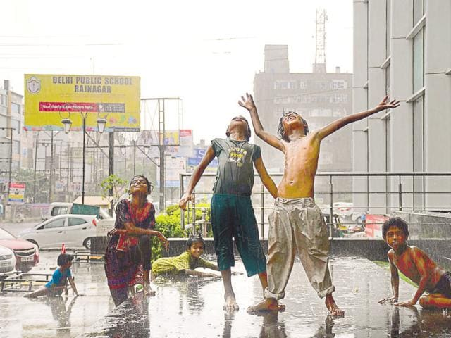 Children in Ghaziabad make the most of the surprise showers on Monday.