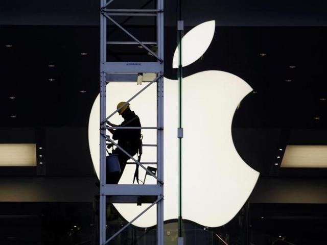 In this file photo, a worker can be seen climbing outside an Apple store in Hong Kong.