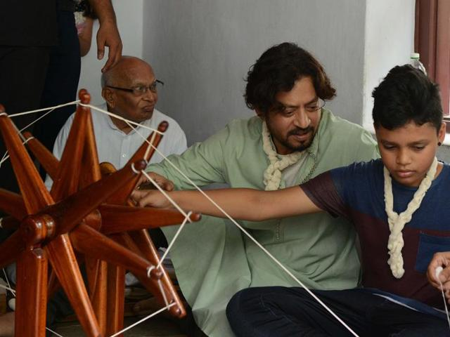 Irrfan Khan watches as his son Aayan learns how to spin thread on a wooden charkha (spinning wheel), helped by a volunteer at the Mahatma Gandhi Ashram in Ahmedabad.