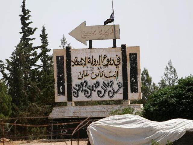 A road sign shows the direction to Manbij city, as seen from the western entrance of the city, in Aleppo Governorate, Syria on sunday. The Arabic reads 'Under the Islamic State rule, you insure your self, money, religion and honour'.