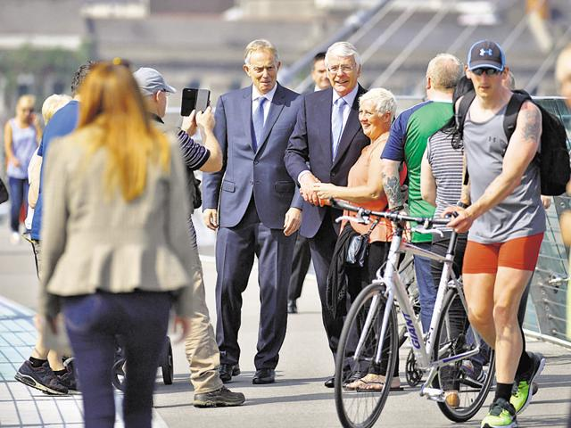 Former British prime ministers John Major (centre, R) and Tony Blair speak to members of the public as they walk across the Peace Bridge, during a visit to share a platform for the Remain campaign event at the University of Ulster in Londonderry, Northern Ireland.