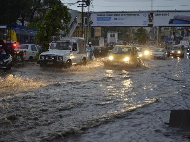 Traffic moves slowly along Jyoti Talkies road in Bhopal on Monday evening after heavy showers lashed the state capital .