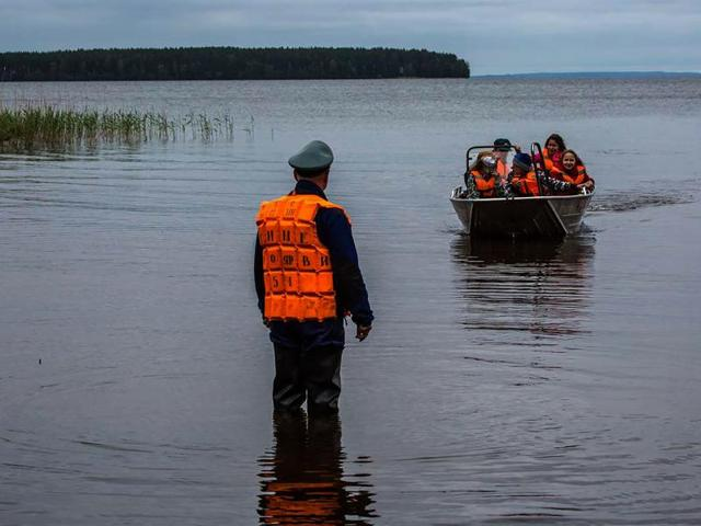 Emergency officers carry  children in a boat on Lake Syamozero in Russia's autonomic republic of Korelia. At least 14 children on a summer camp in northeast Russia drowned when their boats capsized in a storm on the lake.