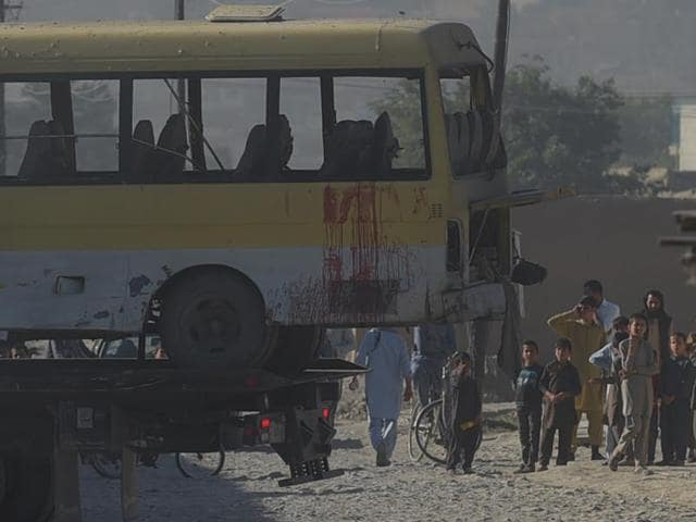 Afghan policemen look at the site of a suicide attack that hit a minibus carrying foreign security guards in Kabul on Monday. Two Indians were among the 14 security guards killed in the bombing.