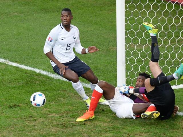 Switzerland's defender Johan Djourou (C) vies on the ground with France's goalkeeper Hugo Lloris (R) beside France's midfielder Paul Pogba (L).