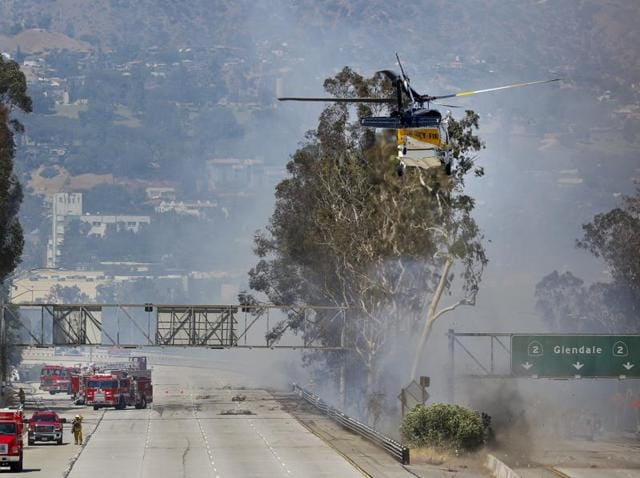 Firefighters use a helicopter to douse a fire near California State Route 2.