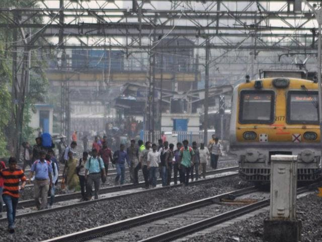 Commuters walk along the tracks between Dadar and Mahim stations on Monday.