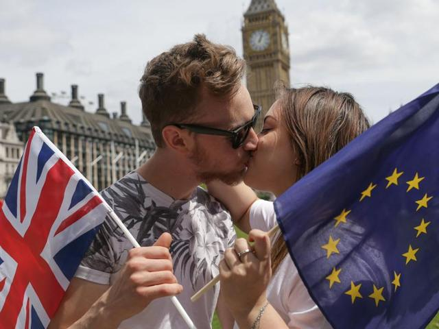 Two activists with the EU flag and Union Jack painted on their faces kiss each other in front of Brandenburg Gate to protest against the British exit from the European Union, in Berlin, Germany, on June 19, 2016.