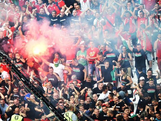Iceland's Kari Arnason and Iceland's Birkir Bjarnason react as Hungary fans throw flares onto the pitch after their first goal.