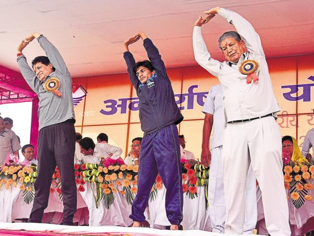 People perform yoga exercises on the occasion of International Yoga Day in Dehradun on Tuesday.