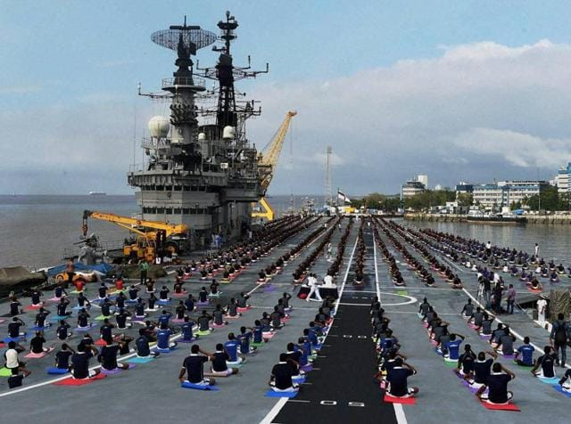 Officers and sailors of the Indian Navy participate in a yoga session on the deck of INS Viraat on the occasion of 2nd 'World Yoga Day' in Mumbai on Tuesday.