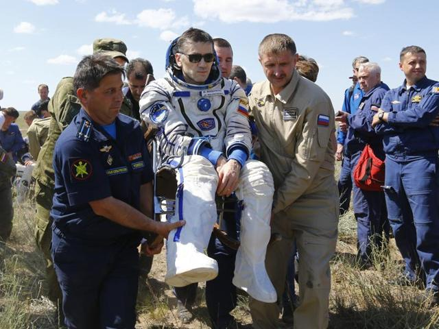 The International Space Station crew, from left, Britain's Tim Peake, Russia's Yuri Malenchenko and Tim Kopra of US, surrounded by ground personnel, rest shortly after landing near the town of Dzhezkazgan, Kazakhstan, on Saturday.