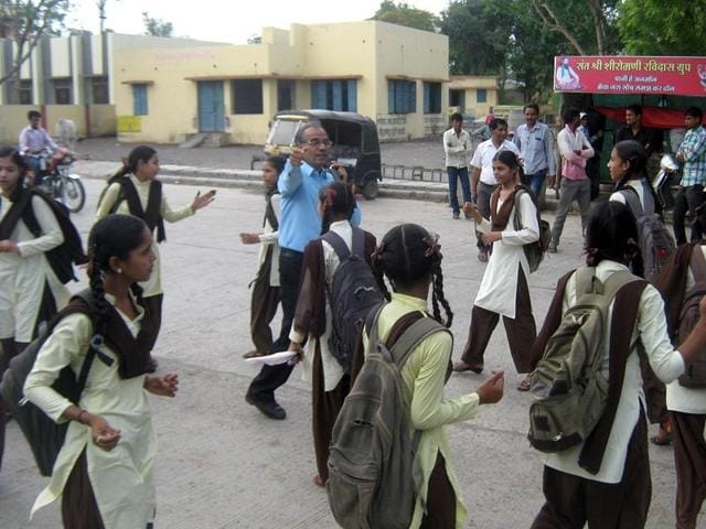 School principal Manohar Lal Rai and his students perform a street play in Shajapur .