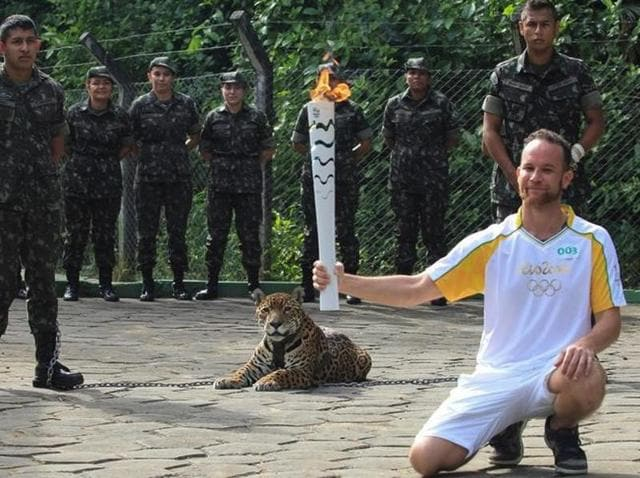 An athlete holds the Olympic Torch near a jaguar --symbol of Amazonia-- during a ceremony in Manaus.
