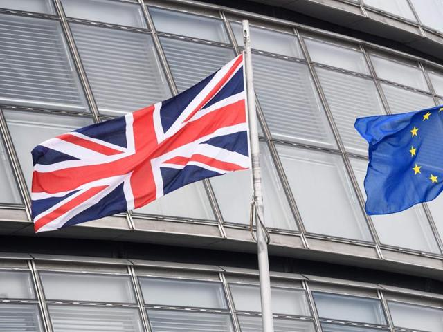This file photo shows The British Union flag (L) and the European Union (EU) flag flying side-by-side outside City Hall, the headquarters of the Greater London Authority, in central London.
