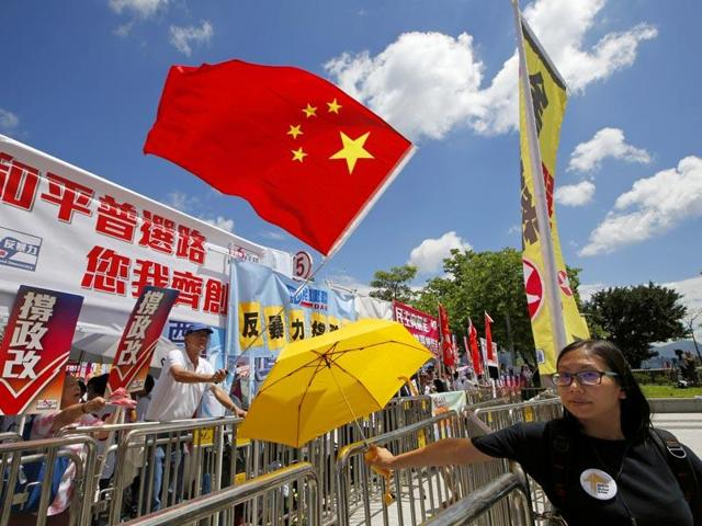 A pro-Beijing protester holding the Chinese national flag confronts a pro-democracy protester carrying a yellow umbrella -- that became movement's symbol. A small faction of pro-independence  supporters have called to return Hong Kong under British rule to escape mainland China's rule.