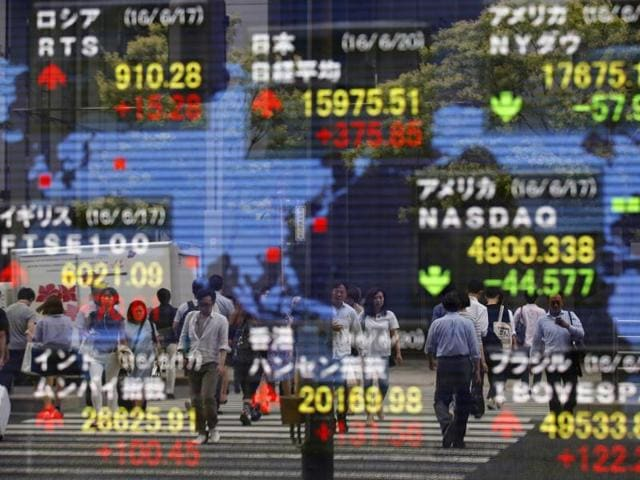 "People are reflected on the electronic stock indicator of a securities firm in Tokyo,  June 20, 2016. Mixed trading across asset classes pointed to uneasiness in markets, investors said, and came after Monday's dramatic surge in ""risk assets,"" driven by polls showing the chance of the United Kingdom leaving the EU appearing to lessen."