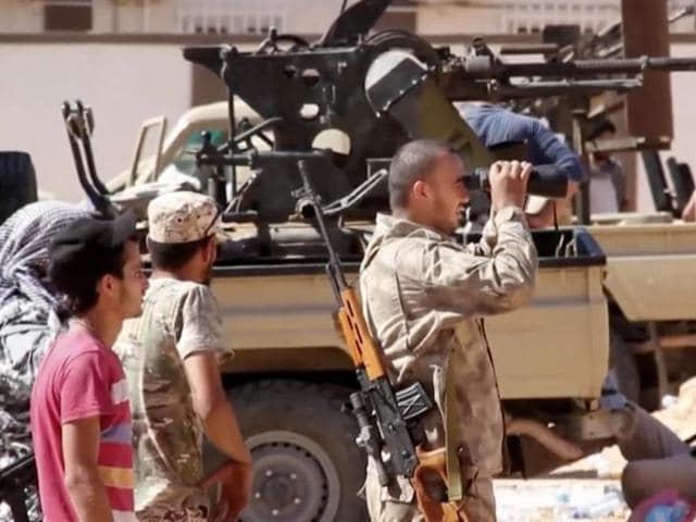 This file photo made from an Associated Press video shows fighters loyal to the unity government on the main street of Sirte.
