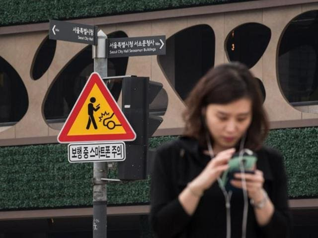 A sign advising pedestrians of the dangers of using smartphones while walking is displayed at an intersection in central Seoul on June 22, 2016.