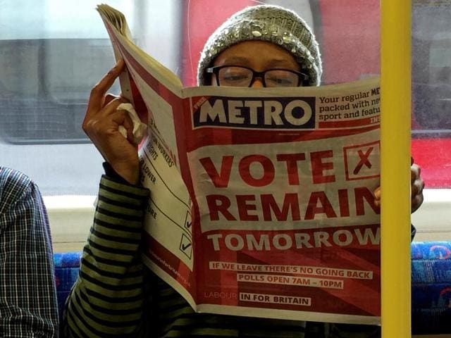 A woman reads a newspaper on the underground in London with a 'vote remain' advert for the BREXIT referendum, Britain June 22, 2016.