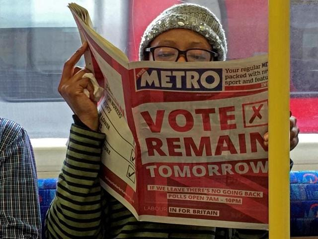 A woman reads a newspaper on the underground in London with a 'vote remain' advert for the BREXIT referendum.