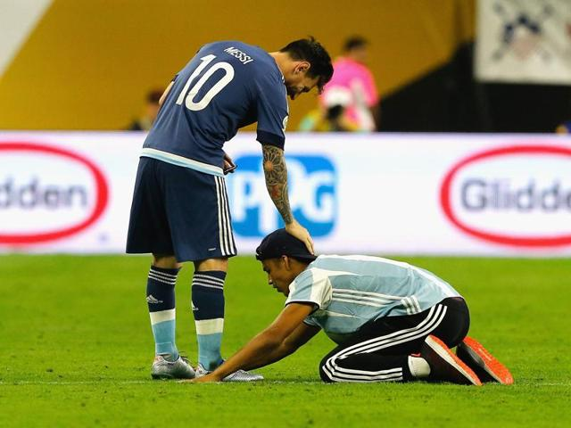 Lionel Messi interacts with a fan who ran onto the field during a 2016 Copa America Centenario semifinal match between Argentina and the United States at NRG Stadium in Houston, Texas.