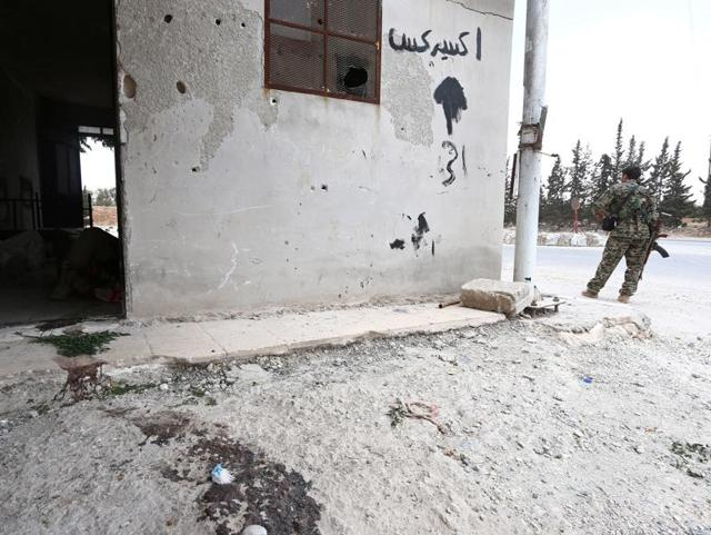 A fighter from the Syria Democratic Forces (SDF) stands near the entrance to a room with a dead Islamic State fighter on the ground, on the western entrance to Manbij city, in Aleppo Governorate of Syria on Tuesday.