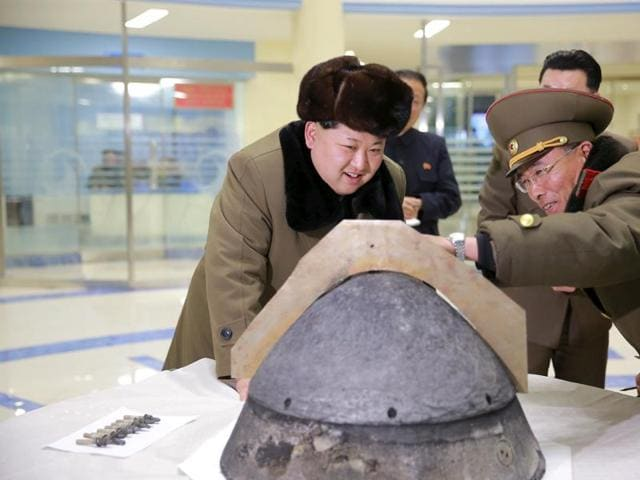 North Korean leader Kim Jong Un looks at a rocket warhead tip after a simulated test of atmospheric re-entry of a ballistic missile, at an unidentified location in this undated photo.