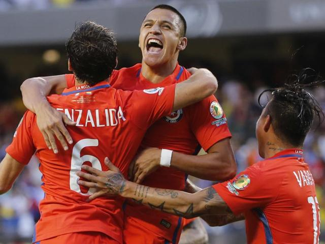 Chile's Jose Pedro Fuenzalida (6) celebrates his goal as he jumps in the arms of Chile's Eduardo Vargas (11).