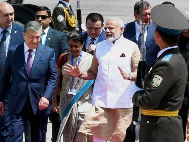 Prime Minister Narendra Modi walks with his Uzbek counterpart Shavkat Miromonovich Mirziyoev upon his arrival in Tashkent on Thursday.