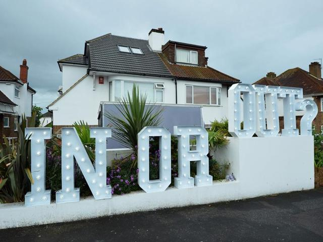An illuminated 'In or Out' sign is pictured outside a house in Hangleton near Brighton in southern England as Britain holds a referendum on wether to stay or leave the European Union (EU).