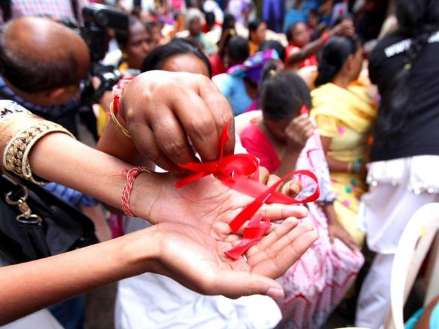 Sex workers distribute red ribbons at a rally on World Aids Day in Mumbai.(HT Photo)