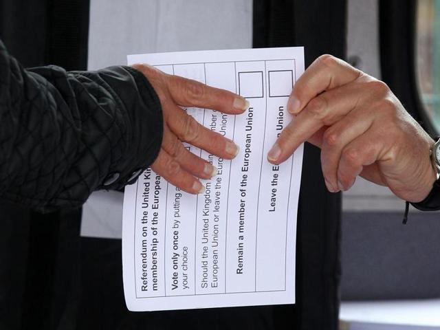 A volunteer hands an unmarked ballot paper to a voter inside a bus being used as a temporary polling station in Kingston-Upon-Hull, northern England, on Thursday, as Britain holds a referendum to vote on whether to remain in, or to leave the European Union (EU).