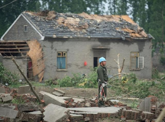 A worker stands among the rubble of destroyed houses after a tornado in Funing, in Yancheng, in China's Jiangsu province.