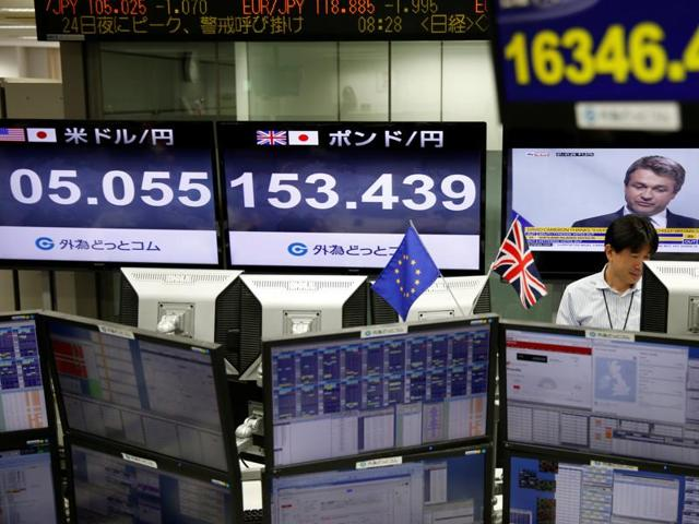 An employees of a foreign exchange trading company works next to monitors displaying television news on Britain's EU referendum, Japan's Nikkei share average (top R), the Japanese yen's exchange rate against British pound (C) and the U.S. dollar (L) in Tokyo, Japan, June 24, 2016.