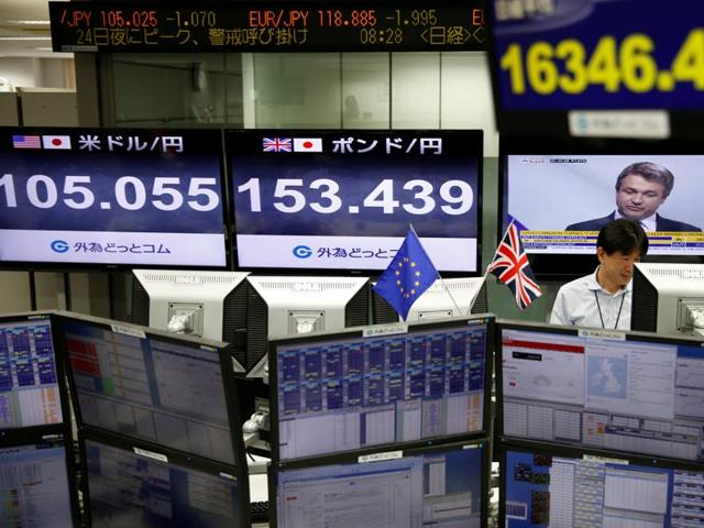 A woman walks past an electronic stock board showing Japan's Nikkei 225 index at a securities firm in Tokyo.