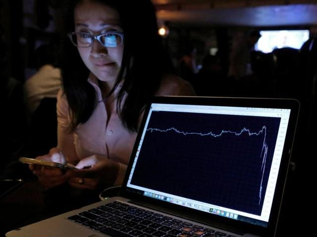 A woman watching the Brexit vote in The Churchill Tavern, a British themed pub, reacts as a graph shows the British Pound falling in value following the announcement that Britain would leave the European Union, in the Manhattan borough of New York, US.