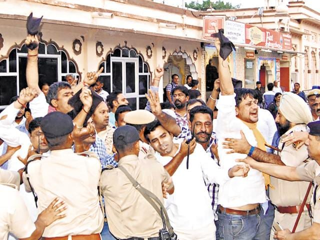 Police officials try to control Congress supporters showing black flags to home minister Gulab Chand Kataria in Bikaner on Friday.